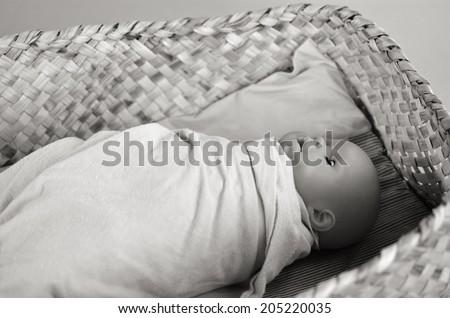 Newborn baby doll sleep in a traditional Maori weaving basket. - stock photo