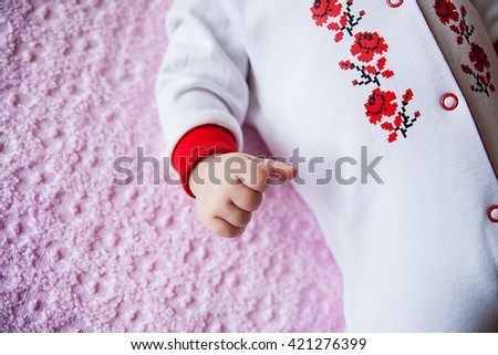 Newborn baby dressed in national costume with embroidery