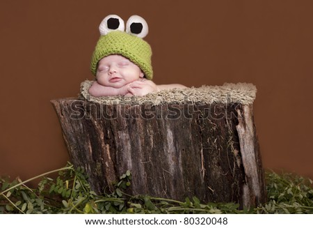 Newborn baby dressed up like tree frog and smiling - stock photo