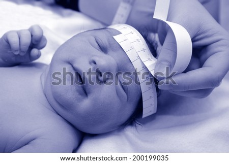 Newborn baby during childbirth examination. - stock photo