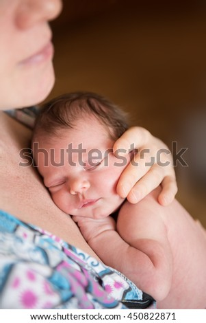 newborn baby fast asleep in his mother's arms