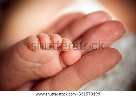 Newborn baby feet in mother hands close up - stock photo
