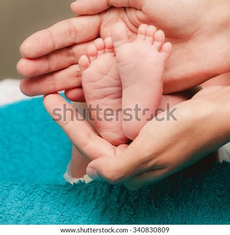 Newborn baby feet in mother hands closeup - stock photo