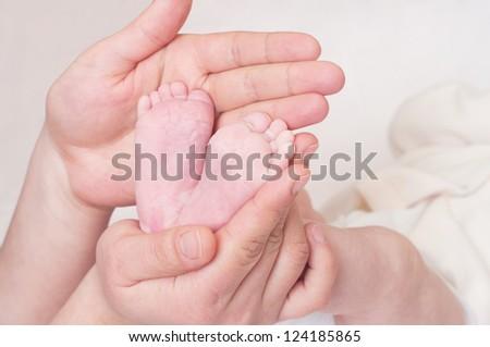 Newborn baby feet in mother's hands - stock photo