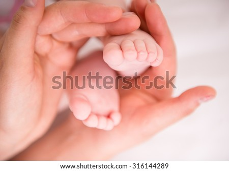 Newborn baby feet in mother's hands on white background.