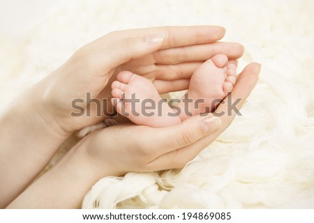 Newborn baby feet mother holding in hands. New born and parent  - stock photo