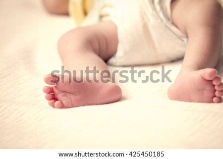 Newborn baby feet on bed in vintage color filter