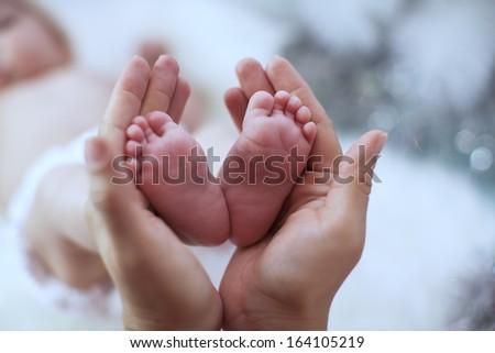 newborn baby feet on female hands - stock photo