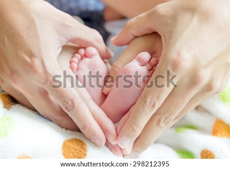 newborn baby feet on mom and dad hands, shape like a lovely heart - stock photo