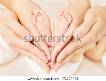 Newborn baby feet parents holding in hands. New born kind and Love symbol as heart sign. - stock photo