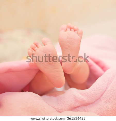 Newborn baby feet sticking out from under the blanket. - stock photo