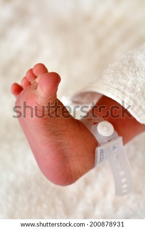 Newborn baby foot with identification bracelet tag name. - stock photo