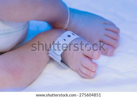 Newborn baby foot with identification hospital tag name under uv  - stock photo