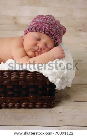 Newborn baby girl, asleep in a wicker basket. - stock photo
