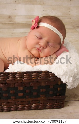Newborn baby girl asleep in a wicker basket. - stock photo