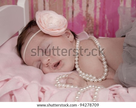 Newborn baby girl asleep in her bed. She is wearing a beautiful pink flowered headband, pearls, and a gray tutu. - stock photo