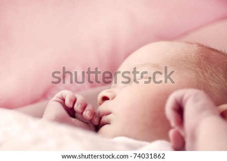 newborn baby girl asleep in her crib - stock photo
