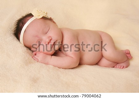 Newborn baby girl, asleep on a blanket. - stock photo
