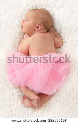 Newborn baby girl asleep on a white blanket. - stock photo