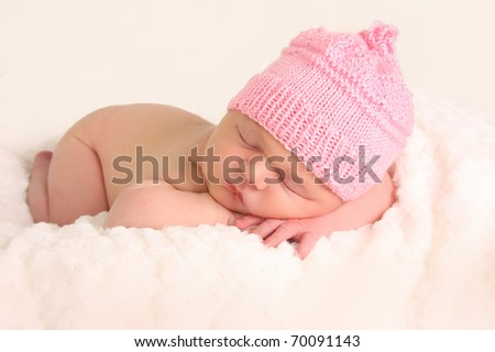 Newborn baby girl in a knitted hat. - stock photo