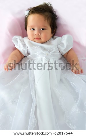 Newborn baby girl in a white baptism dress on a pink blanket - stock photo
