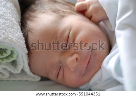 Newborn baby girl in hospital bed sleeping and smiling. Caucasian female.