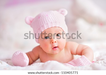 newborn baby girl in pink knitted bear hat and mittens on a bed - stock photo