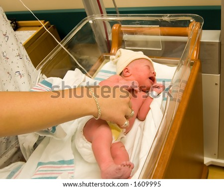Newborn baby girl in warmer only hours after birth. Nurse checks her temperature. - stock photo