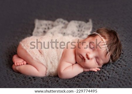 Newborn baby girl in white shawl set - stock photo