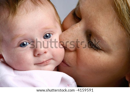 Newborn baby girl kissed tenderly by her mom. - stock photo
