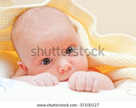 Newborn baby girl lying under yellow towel - stock photo