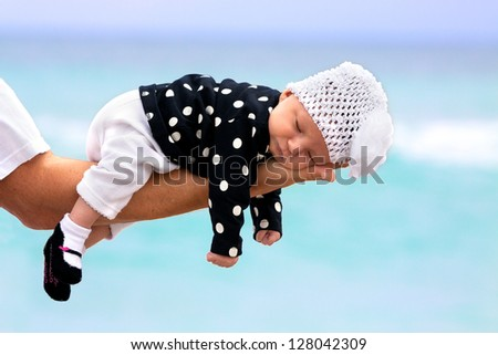 Newborn baby girl of one month, sleeping in father's hand.Ocean background blue and turquoise. Concept of the image is ;protection, love, confidence.