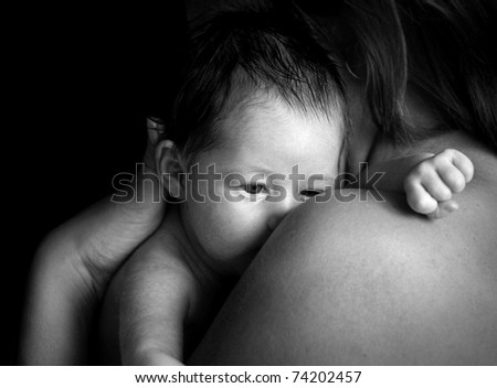 Newborn baby girl on his Mothers shoulder - stock photo