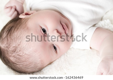 Newborn baby girl playing on a white blanket.