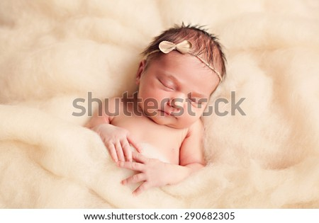 Newborn baby girl posing in fluffy wool - stock photo