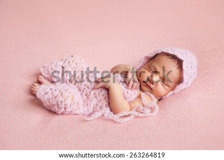 Newborn baby girl posing on pink background