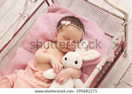 Newborn baby girl posing with soft rabbit - stock photo
