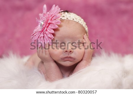 Newborn baby girl sleeping in a adorable position. Bright pink background and flower in hair. - stock photo