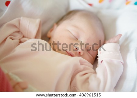 Newborn baby girl sleeping in her crib, lit by the morning sun - stock photo