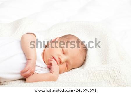 Newborn baby girl sleeping on a white blanket - stock photo