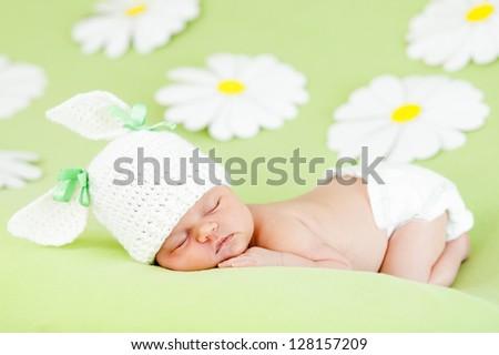 newborn baby girl sleeping on green meadow among flowers - stock photo