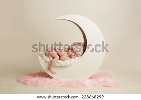 Newborn baby girl sleeping on the moon - stock photo