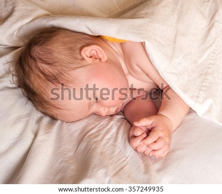Newborn baby girl waking up in the morning in white sheet