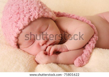 Newborn baby girl wearing a pink knitted elf hat. - stock photo