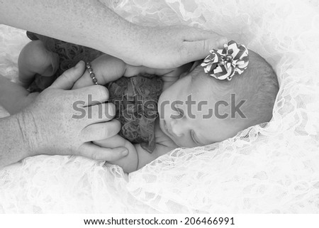 Newborn baby girl with a white lace background. - stock photo