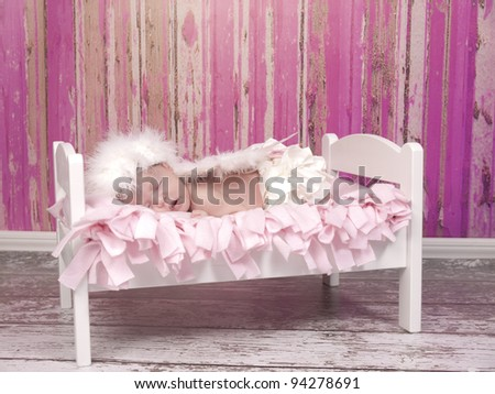 Newborn baby girl with feathered halo and wing's asleep in her bed she look's like and angel. - stock photo