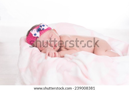 Newborn baby girl with white and pink blanket and headband with bow sleeping - stock photo