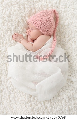 Newborn baby girl wrapped in vintage lace, wearing a pink knitted hat. - stock photo