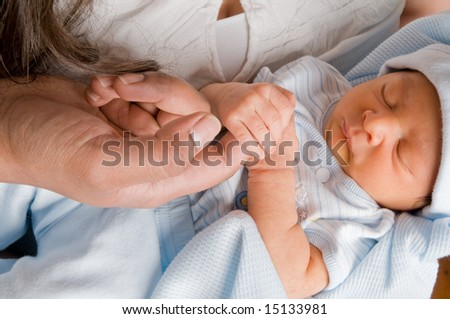 newborn baby grasps father's finger