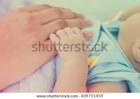 newborn baby hand on mother hand with blue blanket in vintage and color filter style : mother day and people concept - stock photo